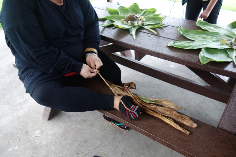 Making some of the cord that was used to tie each package, the same process is used to create the necklaces we were given.